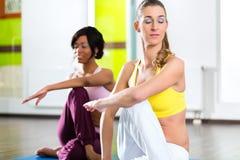 Las mujeres en el gimnasio que hace yoga ejercitan para la aptitud imágenes de archivo libres de regalías