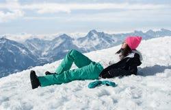 Las mujeres en las montañas en invierno mienten en nieve fotos de archivo