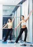 Las mujeres en los aeróbicos ejercitan con la tarjeta del paso de progresión de la aptitud Foto de archivo