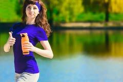 Las mujeres en ropa del deporte están sosteniendo una botella de agua, pareciendo ausentes y de sonrisa, colocándose en la playa  Fotografía de archivo libre de regalías