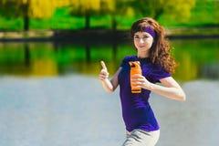 Las mujeres en ropa del deporte están sosteniendo una botella de agua, pareciendo ausentes y de sonrisa, colocándose en la playa  Imagen de archivo