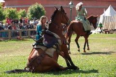 Las mujeres en ropa medieval se preparan en un caballo que se sienta como un perro Fotos de archivo