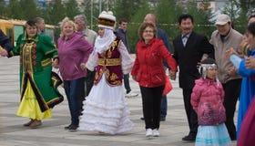 las mujeres en trajes nacionales bailan en una danza redonda Fotografía de archivo