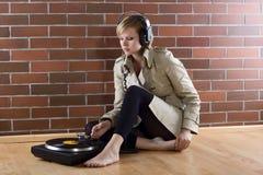 Las mujeres en trenchcoat escuchan música imagenes de archivo