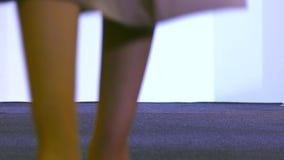 Las mujeres en vestidos muestran el traje en el podio almacen de metraje de vídeo