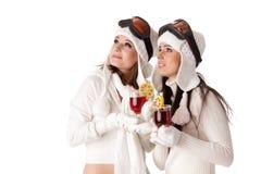 Las mujeres en vidrios del esquí beben el vino reflexionado sobre. imágenes de archivo libres de regalías