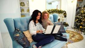 Las mujeres encantadoras comunican con los padres en Internet a través del ordenador portátil, sentándose en el sofá en sala de e almacen de video