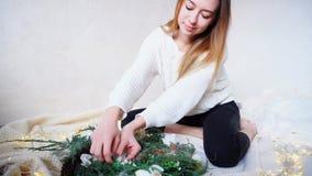 Las mujeres encantadoras preparan decoraciones de la Navidad con su propia mano Imagen de archivo libre de regalías