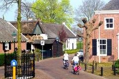 Las mujeres están completando un ciclo en el Kerkebuurt antiguo en Soest, Países Bajos Imagenes de archivo