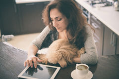 Las mujeres están descansando con un perro en casa y están utilizando la tableta Fotos de archivo