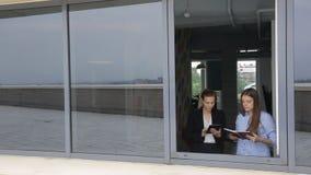 Las mujeres están discutiendo problemas de negocio delante de la ventana abierta almacen de metraje de vídeo