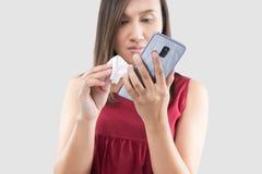 Las mujeres están limpiando el cuerpo del smartphone con un paño de la microfibra fotografía de archivo libre de regalías