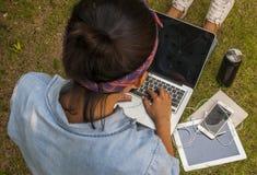 Las mujeres están utilizando los ordenadores portátiles en el jardín fotografía de archivo