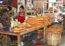 Las mujeres están vendiendo los baguettes franceses frescos originales en el mercado en Vientián en Laos Foto de archivo libre de regalías