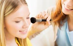 Las mujeres felices con la aplicación del cepillo del maquillaje se ruborizan Fotos de archivo libres de regalías