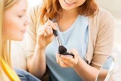 Las mujeres felices con la aplicación del cepillo del maquillaje se ruborizan Foto de archivo libre de regalías