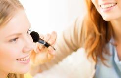 Las mujeres felices con la aplicación del cepillo del maquillaje se ruborizan Imágenes de archivo libres de regalías