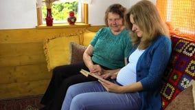 Las mujeres felices de la familia tienen libro de lectura de la diversión almacen de metraje de vídeo