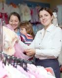 Las mujeres felices eligen desgaste en el departamento de la ropa. Foco en mujer Fotos de archivo libres de regalías