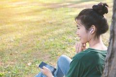 Las mujeres felices escuchan la música en smartphone Imagen de archivo