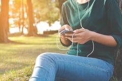 Las mujeres felices escuchan la música en smartphone Imágenes de archivo libres de regalías
