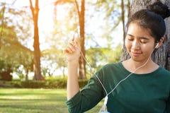 Las mujeres felices escuchan la música en smartphone Imagen de archivo libre de regalías