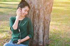 Las mujeres felices escuchan la música en smartphone Fotos de archivo