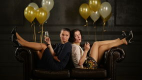 2f2890d05 Las mujeres felices están bebiendo el alcohol durante un partido Dos  señoras en tacones altos y