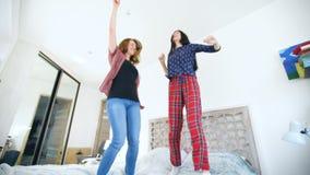 Las mujeres felices jovenes juntan el baile sobre una cama con los auriculares y se divierten en dormitorio en casa almacen de video