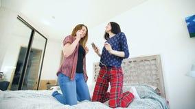 Las mujeres felices jovenes juntan el baile sobre una cama con los auriculares y se divierten en dormitorio en casa metrajes