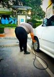 Las mujeres gordas están llenando el neumático en la bomba imagen de archivo