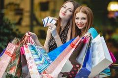 Las mujeres hacen compras con las tarjetas de crédito en la alameda Imagen de archivo