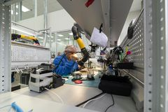 Las mujeres hacen soldar de los componentes de radio a los tableros electrónicos Planta para la producción de equipo electrónico Fotos de archivo