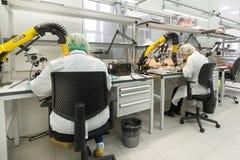 Las mujeres hacen soldar de los componentes de radio a los tableros electrónicos Planta para la producción de equipo electrónico Fotografía de archivo libre de regalías