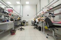 Las mujeres hacen soldar de los componentes de radio a los tableros electrónicos Planta para la producción de equipo electrónico Imagenes de archivo