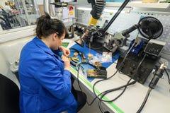 Las mujeres hacen soldar de los componentes de radio a los tableros electrónicos Planta para la producción de equipo electrónico Fotografía de archivo