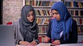 Las mujeres hermosas en diverso hijab se están sentando en biblioteca cerca del ordenador portátil y hablar concentrado con la he metrajes