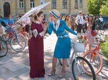 Las mujeres hermosas en la vieja moda visten hablar de la bicicleta del vintage durante travesía retra del festival al aire libre Fotos de archivo libres de regalías