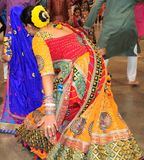Las mujeres hermosas están bailando en la acción Disfrutando del festival hindú de llevar de Navratri Garba tradicional consuma fotos de archivo