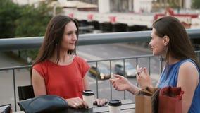 Las mujeres hermosas que beben el café comunican en un café con vistas al tráfico, hablando después de hacer compras 4K