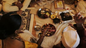 Las mujeres indias lanzan el arroz sobre las placas con especies almacen de metraje de vídeo