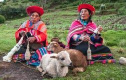 Las mujeres indias peruanas en ropa tradicional tejen un hilado, sentándose en una hierba cerca de ovejas Fotografía de archivo libre de regalías