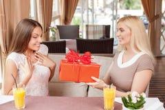 Las mujeres jovenes alegres están celebrando en café Fotografía de archivo libre de regalías