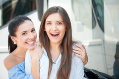 Las mujeres jovenes alegres están viajando por el público Fotos de archivo