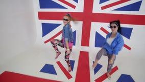 Las mujeres jovenes atractivas en entrenamiento de las gafas de sol bailan la mudanza en estudio con la bandera BRITÁNICA metrajes