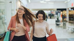 Las mujeres jovenes atractivas están caminando en centro comercial con los bolsos, están mirando alrededor, están hablando y está almacen de metraje de vídeo