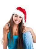 Las mujeres jovenes atractivas se sientan en el sombrero de Papá Noel Fotografía de archivo libre de regalías