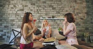 Las mujeres jovenes atractivas tienen un buen rato de la pizza del tiempo para un sleepover sobre la señora que trae las cajas en almacen de metraje de vídeo