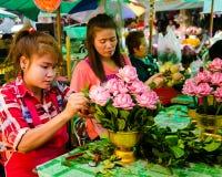 Las mujeres jovenes crean arreglos florales en un mercado al aire libre en Bangkok Fotografía de archivo libre de regalías