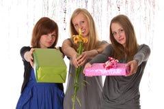 Las mujeres jovenes dan el regalo y la flor Foto de archivo libre de regalías